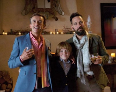 A man in a blue suit jacket and pink shirt and a man in a blazer with a patterned scarf pose for a family photo with a young boy