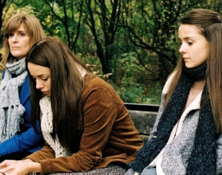 A woman and her two teenage daughters sit on a bench looking solemn
