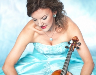 Tasmin Little wears a blue ball gown and holds her violin.