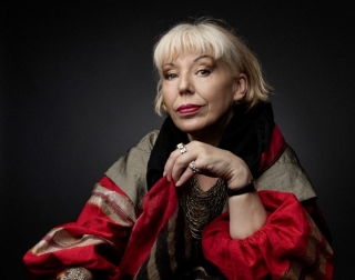 Barb Jungr in a red and gold puffy coat against a black background