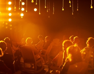 People sitting on rocking chairs in a dark room with light bulbs hanging from the ceiling