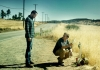 An image of a man standing by the side of a road while another man crouches down presenting an object to him