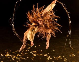 A dancer dressed in brown and gold jumping in the air against a black background
