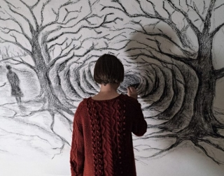 A girl in a red jumper drawing a dark forest on a white wall