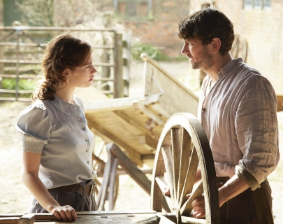 A man and a woman stand by a spinning wheel looking at each other