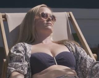 A blonde woman in a blue bathing suit lying down sunbathing