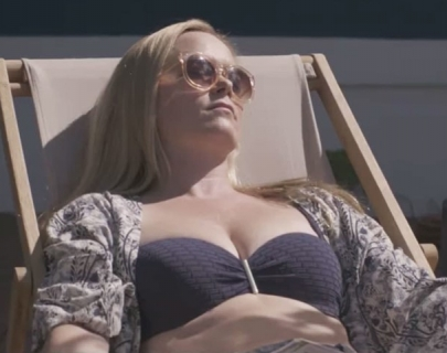 A blonde woman in a blue bathing suit lying down sunbathing