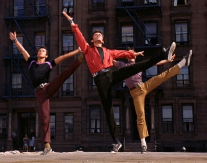 Three men doing high kicks with their arms in the air with a building behind them. The man in the middle wears a bright red shirt.