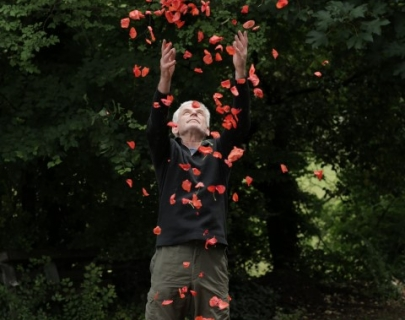 A man throwing red petals in the air in an outdoor setting