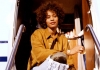 Whitney Houston sits on a step in the sun wearing a golden brown shirt and squinting into the camera