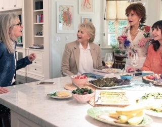 Four women laugh together in a kitchen, with food and wine.