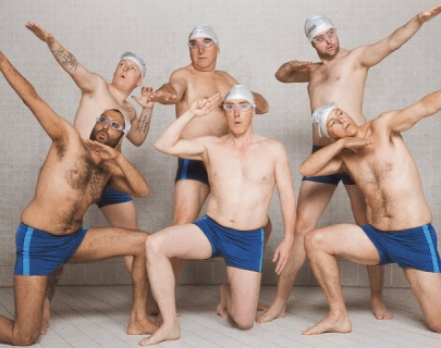 A group of men in swimming hats, googles and blue trunks pose at the poolside