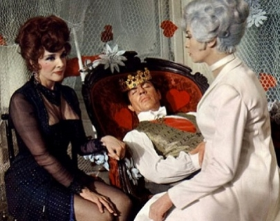 A man wearing a crown lies on a red seat, and two women sit next to him.