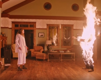 A woman stands in her living room, terrified by the appearance of a flaming figure.