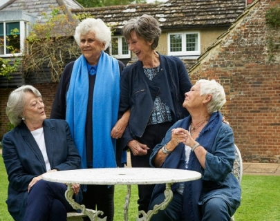 Actresses and Dames Maggie Smith, Judi Dench, Eileen Atkins, Joan Plowright talk and laugh in a garden.