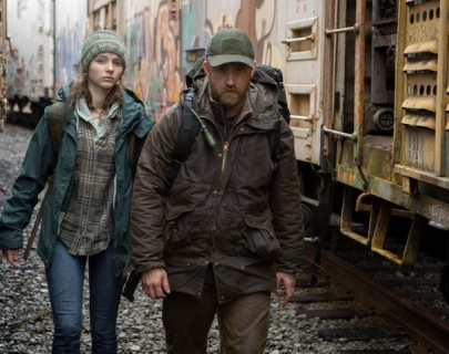 A man and girl walk between train cars, wearing hats, waterproof jackets and rucksacks