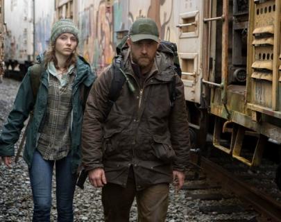 A man and girl walk between train cars, wearing hats, waterproof jackets and rucksacks