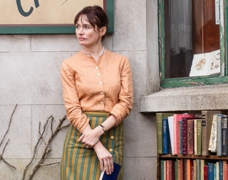 A woman stands outside her bookshop, wearing a peach blouse, and a yellow and green skirt