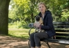 A blonde woman sits on a bench holding a pug.