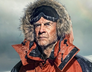 Explorer Sir Ranulph Fiennes, wearing a hooded jacket and goggles in the snow.
