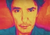 A close crop on comedian Dylan Moran, which has been coloured in oranges, pinks and blues