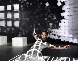 A dancer dressed in white surrounded by digital projections of white cubes against a black background