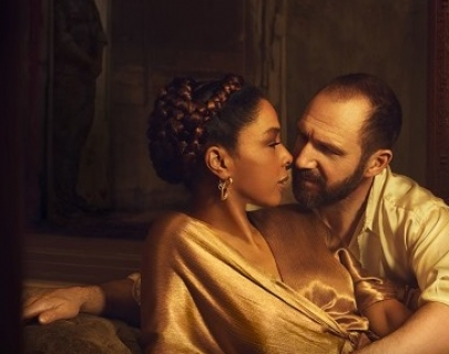 A white man and a black woman in gold clothes lounging in an embrace