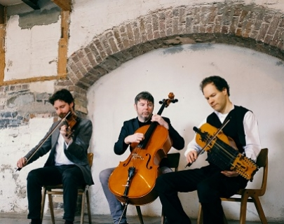 Three musicians sit in front of exposed brickwork, playing a fiddle, cello and nyckelharpa