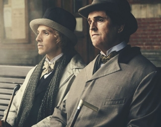 Two men sit on bench wearing Victorian clothes and top hats