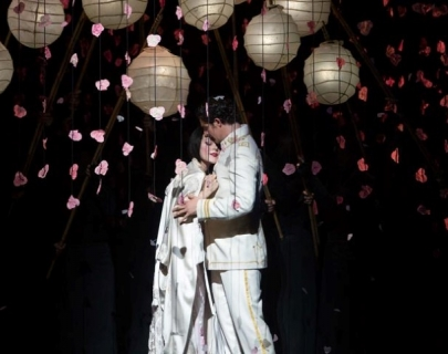 A woman in a white kimono and a man in a white Navy uniform stand under lanterns and falling petals.