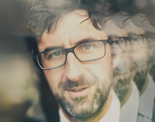 A closeup image of Mark Watson with reflected images behind him