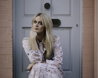 Dolly Alderton sits on a doorstep wearing a spotty dress. Credit: Jo Bongard
