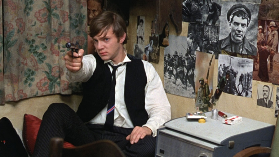Young boy wearing a school uniform pointing a revolver at someone offscreen