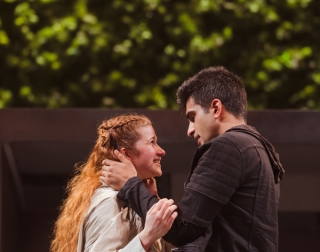 a girl with ginger hair and a white jacket and boy with black hair and a black jacket embrace in front of a green background