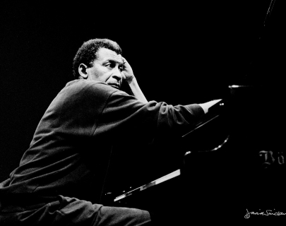 Black and white image of Abdullah Ibrahim sitting at a piano.