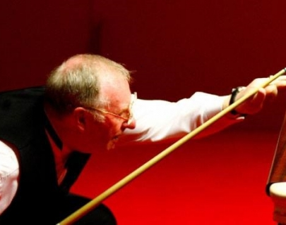 Dennis Taylor holding a snooker cue preparing to take a shot