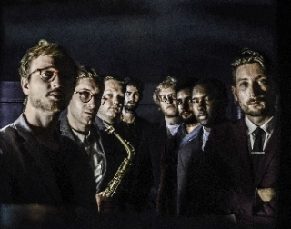 A group of mean wearing cool suits stand looking into the camera against a dark background. One holds a saxophone.