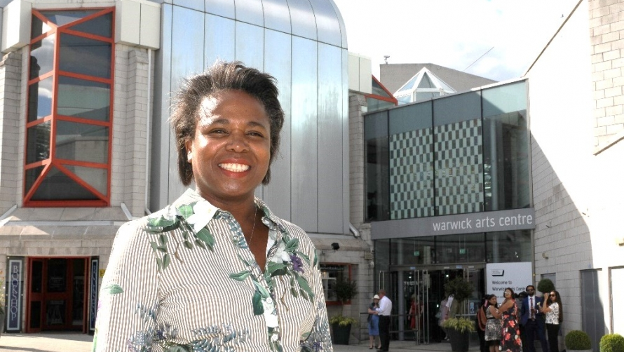 Doreen Foster standing outside Warwick Arts Centre in the sun