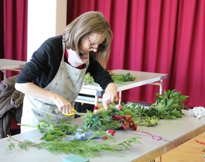 A woman stands at a table cutting flowers and shaping a Christmas wreath