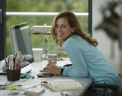 Adele Parks leans, smiling, over a computer computer keyboard