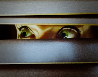 A woman's large, green eyes peer out of some blinds