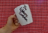 """A white mug with the writing """"The Welcome Revolution"""" against a red gingham background"""