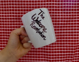 "A white mug with the writing ""The Welcome Revolution"" against a red gingham background"