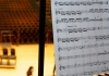 A sheet of music in focus against an out of focus view of the Butterworth Hall