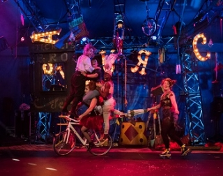 Four women ride a bicycle pushed by another actress while the circus props are in suspension in the air around them