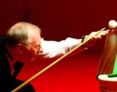 Dennis Taylor holding a snooker cue and preparing to perform a trick shot