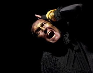 A man in black against a black background grasps his head in anguish