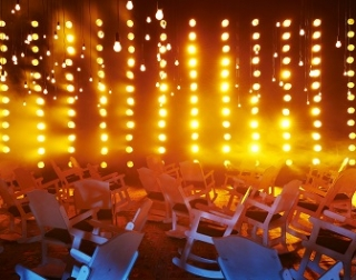 A large room filled with rocking chairs are lit by many hanging orange bulbs
