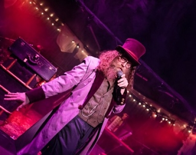 A man with a large beard and a top hat speaks into a mic, lit by purple lighting