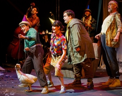 Four performers, two female and two male, in colourful clothes, stand in a line behind a puppet of a white duck